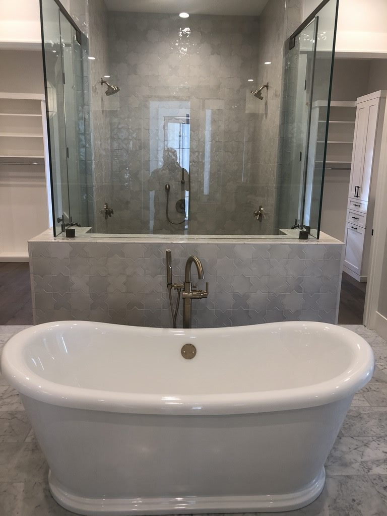 Bath tub in a newly remodeled bathroom with a gray tile shower
