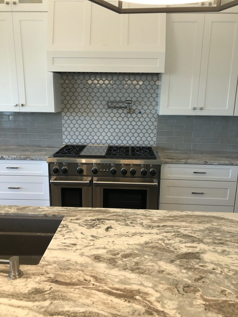 Grey and white marble counter top in kitchen with a glass tile backsplash behind the stove