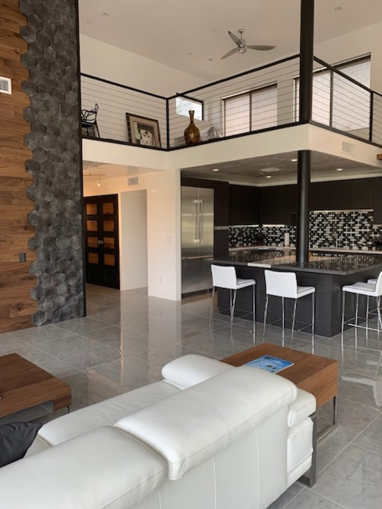 two story clubhouse with extra large tile floors, a wood and tile decorative wall, black stone counter tops, and a black and white glass backsplash
