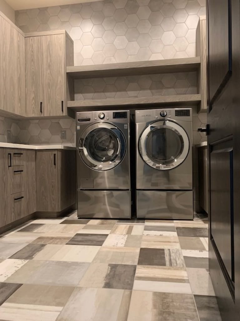 white and gray colored tiles in laundry room with a hexagon patterned decorative tile wall