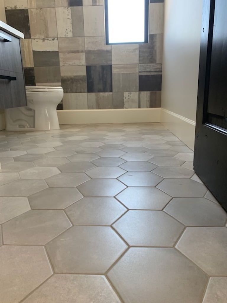 Hexagon shaped grey floor tiles and a multi colored tile decorated shower