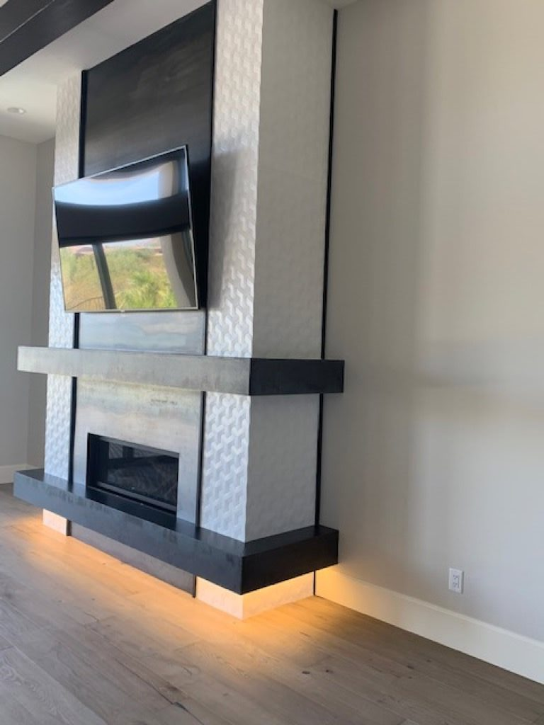 Ceramic white tile and gray ledge surrounding fire place and mounted tv