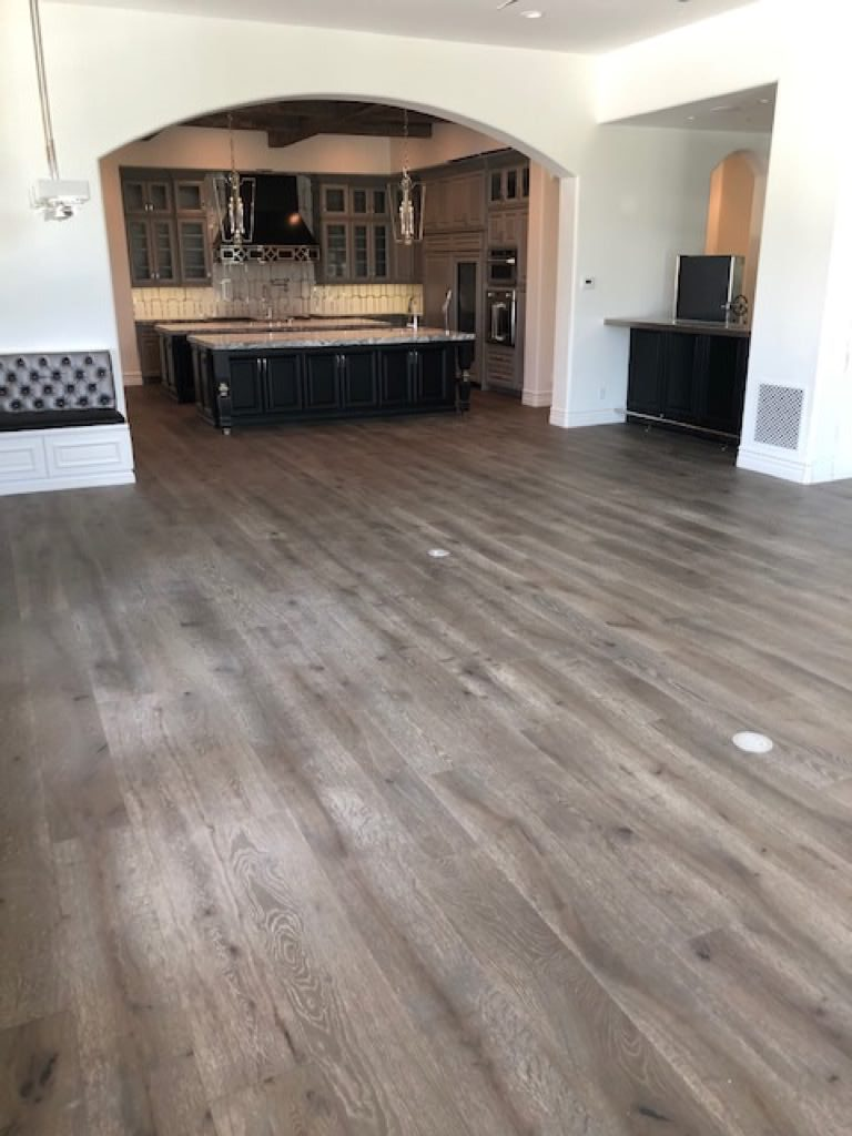 Hardwood floors in living room leading to a kitchen