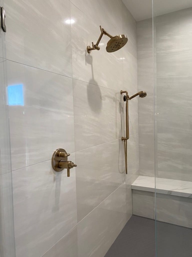 Stone colored tile shower with bench