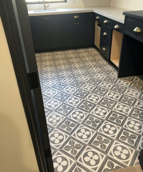 White and gray floral patterned cement tile in laundry room