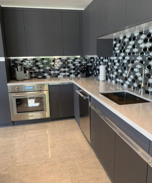 White stone kitchen counter top with a black and white glass tile backsplash