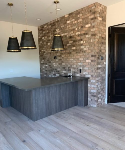 Dark gray stone counter top bar with a tile decorative wall