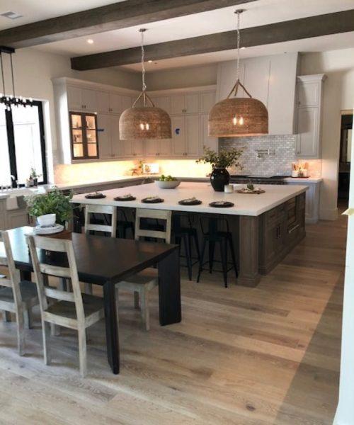 Light grey hardwood floor kitchen with stone counter top island and ceramic tile backsplash