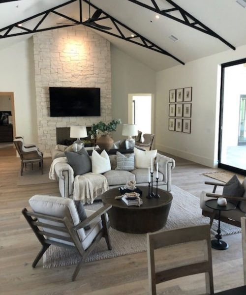 Light grey hardwood floors in living room with a tile decorated feature wall with tv